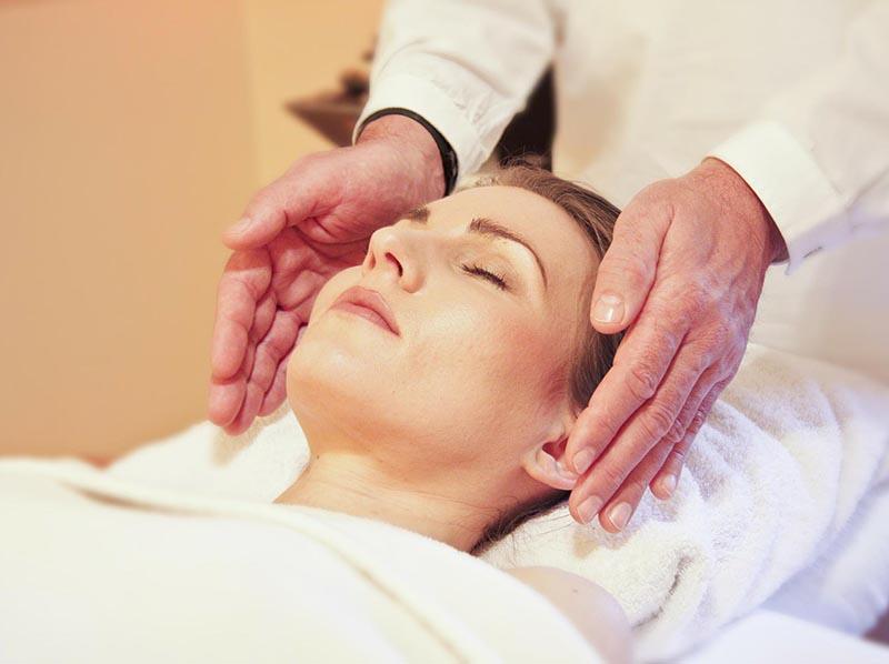 mains allant faire un soins du visage à une femme couchée