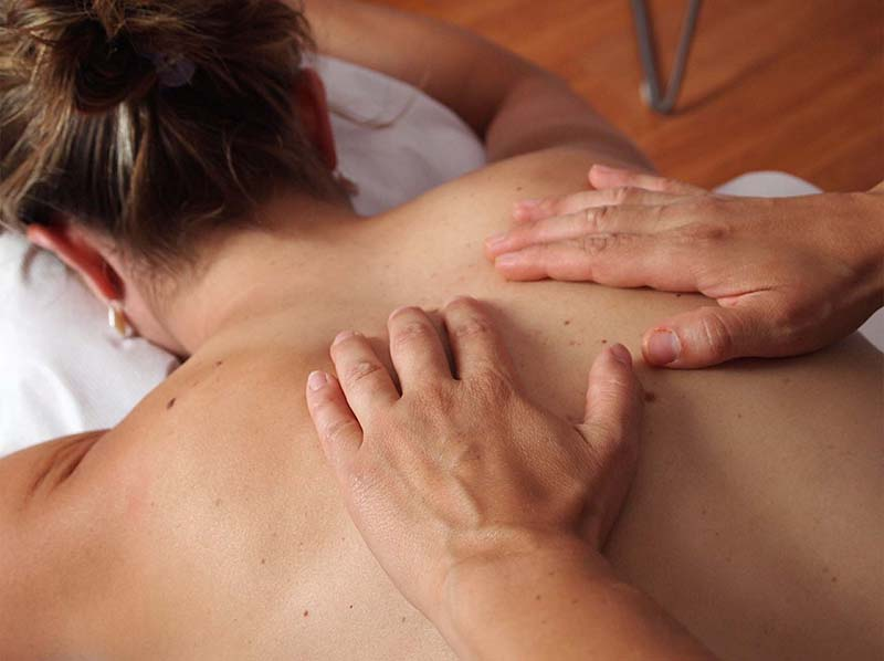 mains entrain de masser le dos d'un homme couché