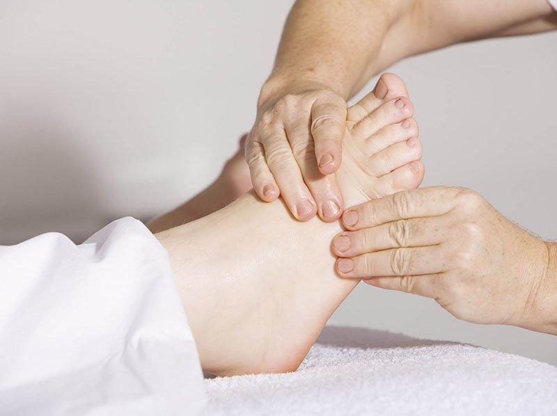 mains faisant un massage à un pied